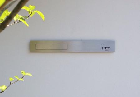 真っ白な漆喰の壁にステンレスがきらりと光るシンプルなサイン