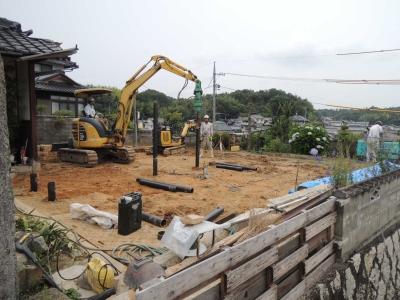 地盤工事にて1本1本の鋼管杭を地面にねじ込む作業